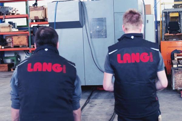 Lang GmbH Professionelle Fachkräfte bewegen eine große MAschine mit Hilfe von Transportrollen bis zu 40 Tonnen Nutzlast